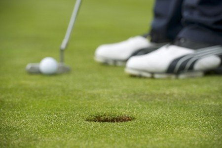 Closeup of a golf player putting at green