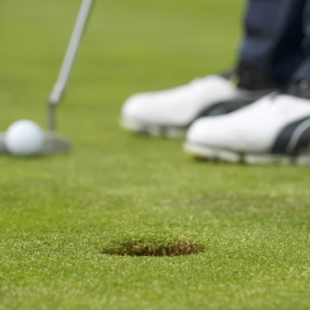 Closeup of a golf player putting at green